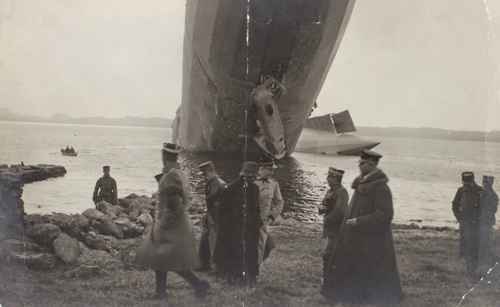 Det strandede luftskib L20 ved den norske kyst nær Stavanger den 3. maj 1916. Personen i jakken med pelskrave til højre i billedet er formodentlig L20´s kaptajn, Stabbert. Omkring ham norske officerer og soldater. (Tønder Zeppelin- og Garnisonsmuseum)