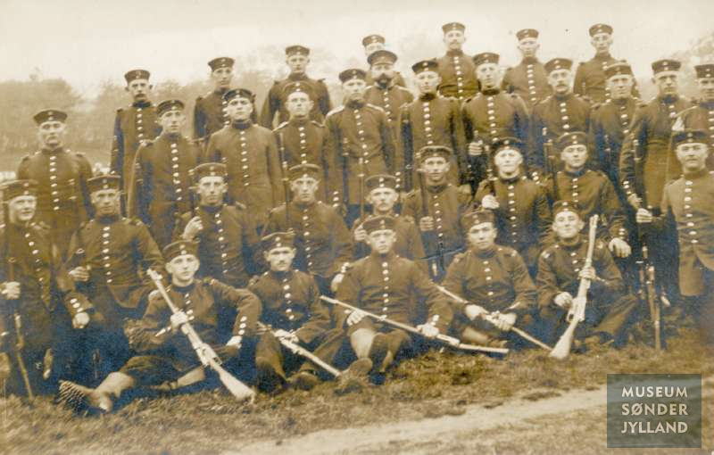 Fotopostkort med motiv af en gruppe tyske soldater, som deltog i 1. Verdenskrig 1914-1918. Knælende i 2. række ses som nr. 4 fra højre Otto Theobald Schwartz fra Skodsbøl, Broager sogn