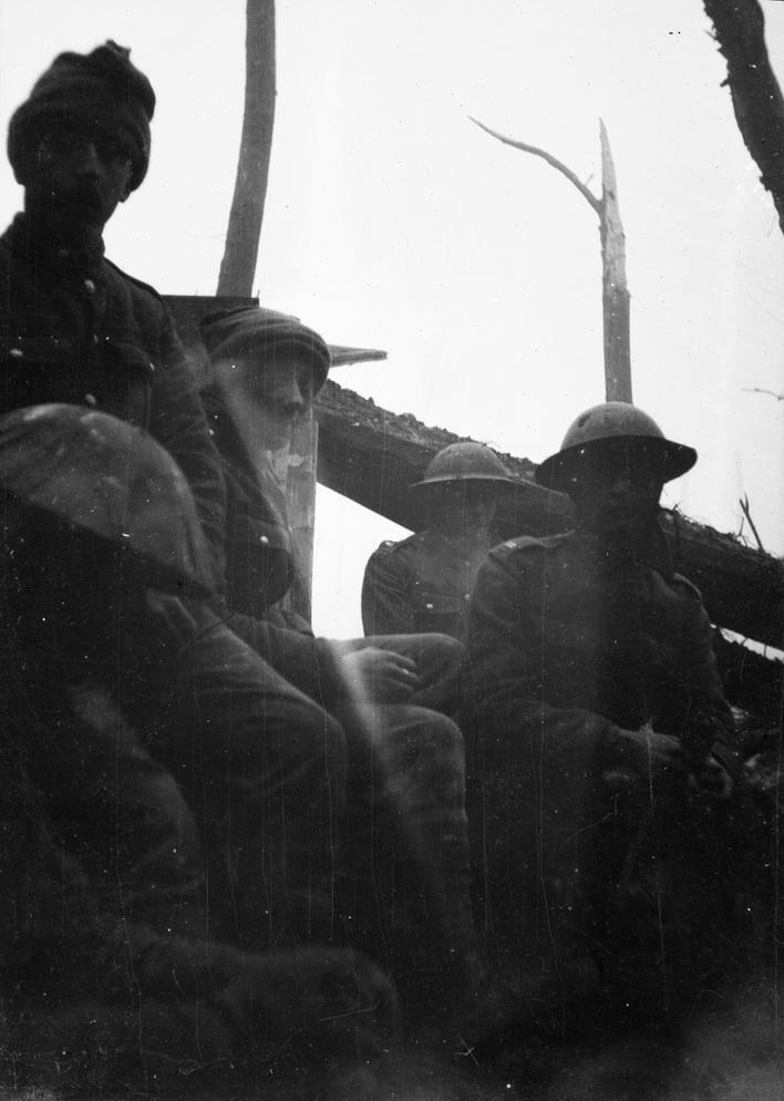 Britiske soldater i en skyttegrav, sted og dato er ukendt, ligesom omstændighederne: sidder de i deres egen skyttegrav eller i en tysk som krigsfanger (billedets snapshot-agtige karakter og manglen på våben kunne tydes i den retning)? Fotoet stammer fra en samling af negativer med motiver fra sidste del af krigen bl.a. af soldater fra Füsilier-Regiment Nr. 86. Negativerne har alle sammen samme format, og må formodes at stamme fra samme kamera, og med mindre der er tale om et erobret kamera med et negativ fra den tidligere, britiske ejer, så må man gå ud fra at fotografen har været tysk. Da de to mænd øverst til venstre bærer huer og ikke hjelme, kunne de være del af en mandskabet fra en kamppatrulje, som den der beskrives i regimentshistorien for Füsilier-Regiment Nr. 86? Deltagere i den type patruljer lagde gerne hjelmen, dels var den tung, dels larmede den, når den stødte mod ting.